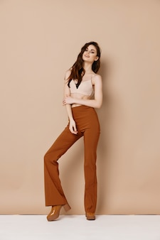 Mulher fofa de calça e camiseta com sapatos de salto alto bege