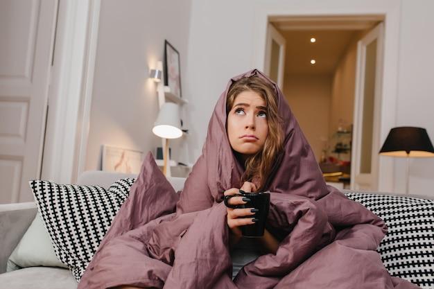 Mulher fofa e preocupada de olhos azuis posando sob a manta roxa e olhando para longe