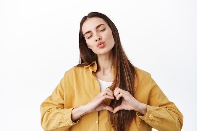 Mulher fofa mostrando seu carinho, fecha os olhos e faz gesto de coração no peito, eu te amo, mandando beijo no ar na frente, te beijando, em pé sobre uma parede branca em camisa amarela