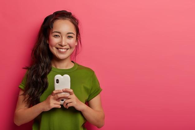 Mulher fofa sorridente com bochechas vermelhas feliz por ler a mensagem do amante, não consigo imaginar a vida sem tecnologias modernas