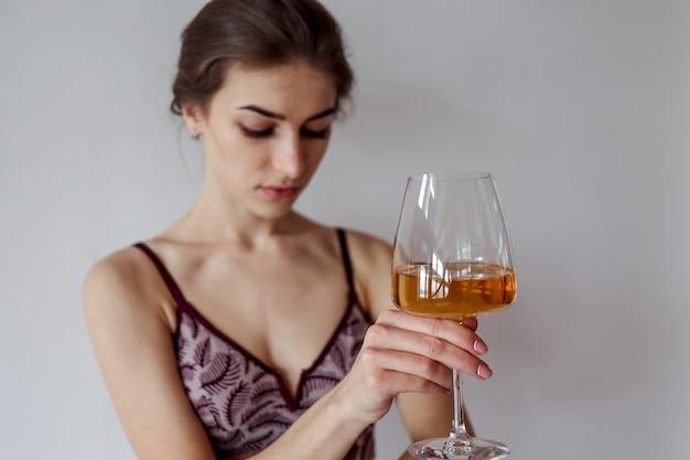 Mulher fofa tomando uma taça de vinho branco