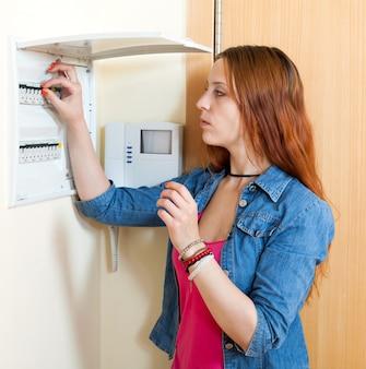 Mulher fofa triste perto do painel de controle de energia