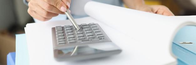 Mulher folheando uma pasta com documentos e olhando para o close da calculadora