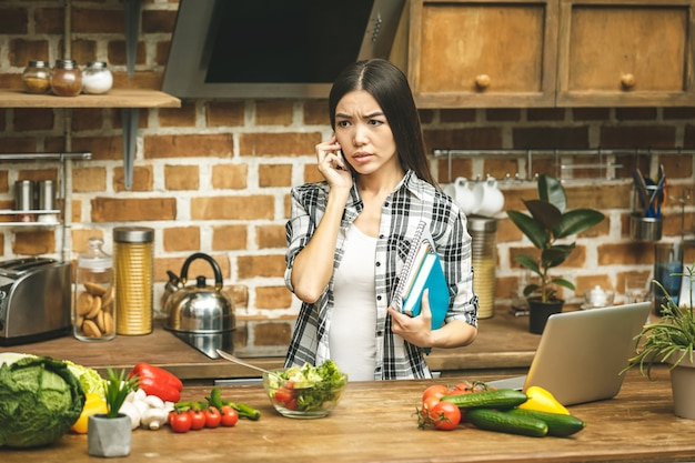 Mulher forçada asiática bonita nova com o portátil na cozinha. trabalhando em casa. em estresse.