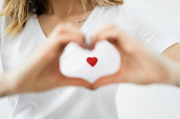 Mulher formando um coração com as mãos