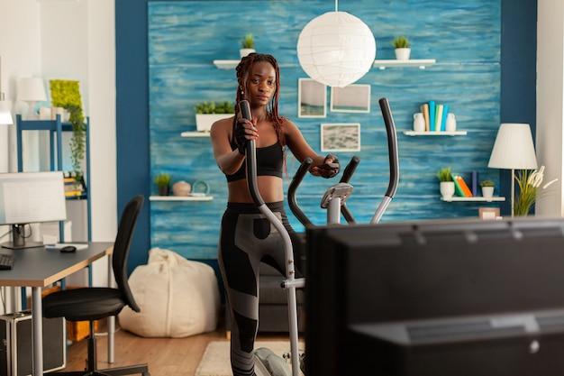 Mulher forte apta africana fazendo exercícios cardiovasculares na máquina elíptica, na sala de estar em casa, olhando para a tv, assistindo as instruções segurando o controle remoto. exercício vestido com roupas esportivas.