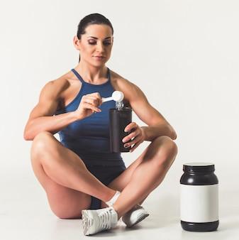 Mulher forte bonita no sportswear que adiciona a nutrição do esporte.