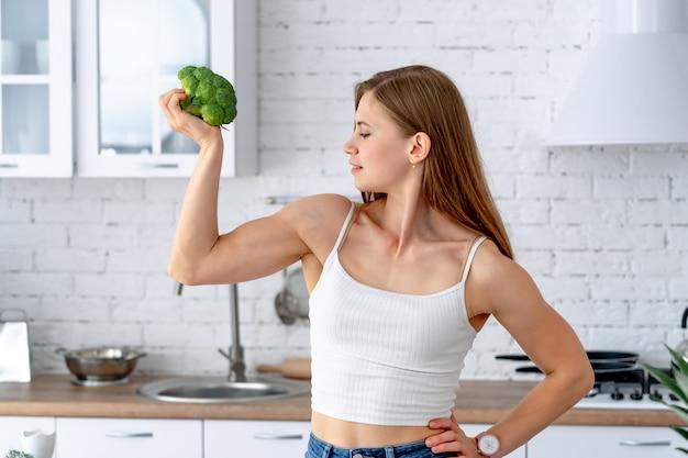 Mulher forte com brócolis na cozinha.
