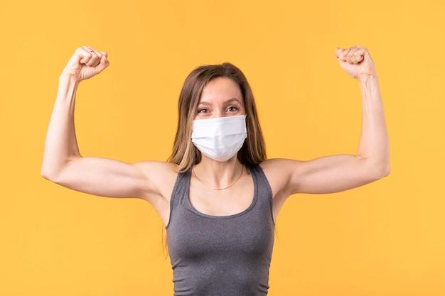 Mulher forte com máscara médica mostrando os músculos