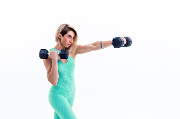 Mulher forte dando socos com halteres nas mãos durante a aula de boxe