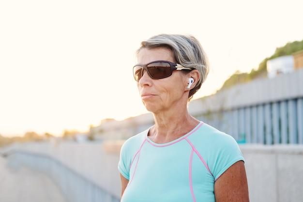Mulher forte de idosos ativos gosta de ouvir música terminar o treino de fitness na cidade com fones de ouvido e óculos de sol. relógio inteligente. mulher de aptidão desportiva. estilo de vida saudável. foto de alta qualidade