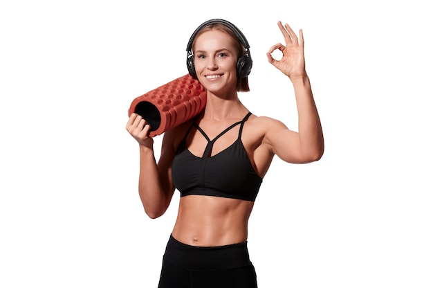 Mulher forte e atlética com rolo de massagem e fones de ouvido mostra gesto ok em fundo branco isolado