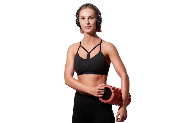 Mulher forte e atlética com rolo de massagem e fones de ouvido no fundo branco isolado