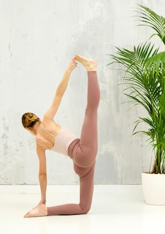 Mulher forte e flexível realizando uma variação vertical da pose de ioga anantasana com divisão completa das pernas