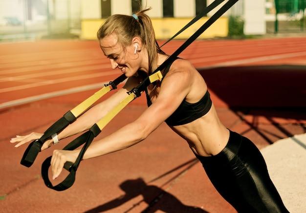 Mulher forte e magra fazendo exercícios com alças de ginástica na pista de um estádio com uma capa vermelha em um dia ensolarado