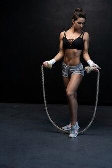 Mulher forte e musculosa com pular corda