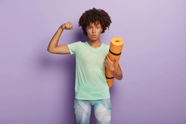 Mulher forte e poderosa levanta o braço, mostra o bíceps, segura o colchonete para treino de ginástica, vestida com roupa ativa