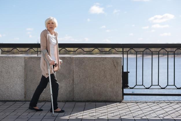 Mulher forte e reflexiva, séria, usando muletas e desviando o olhar enquanto caminha perto do rio