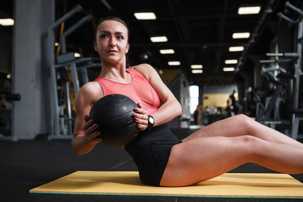 Mulher forte e saudável feliz fazendo exercícios abdominais com torção russa com medicine ball na academia