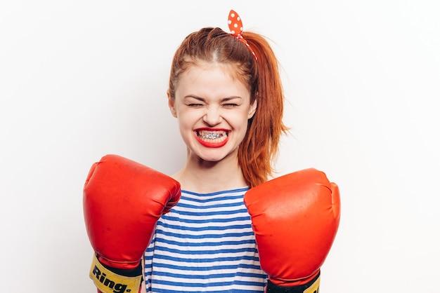Mulher forte em luvas de boxe vermelhas e em uma camiseta listrada vista frontal de fundo claro