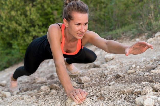 Mulher forte escalando com as próprias mãos