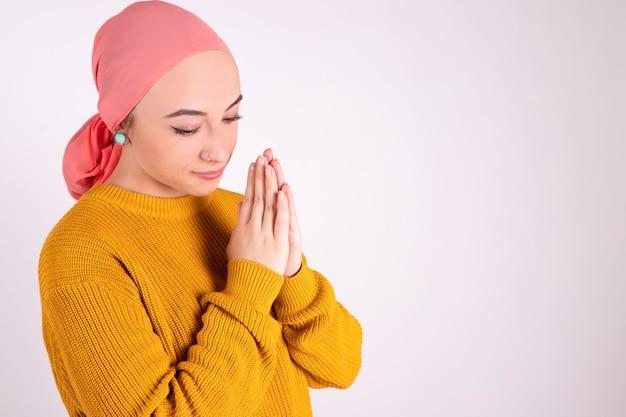 Mulher forte, lutando contra o câncer, rezando com as mãos