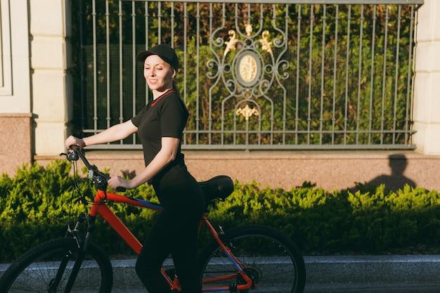 Mulher forte morena atlética jovem em uniforme preto, boné pare de andar de bicicleta preta com elementos laranja ao ar livre em dia ensolarado de primavera ou verão. fitness, esporte, conceito de estilo de vida saudável.