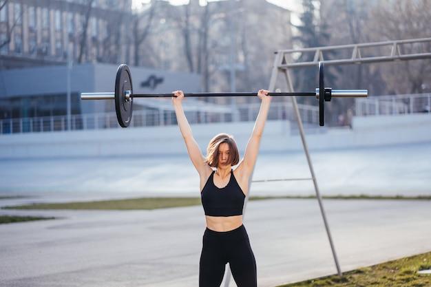 Mulher forte se exercitando com o conceito de fitness esportivo com barra