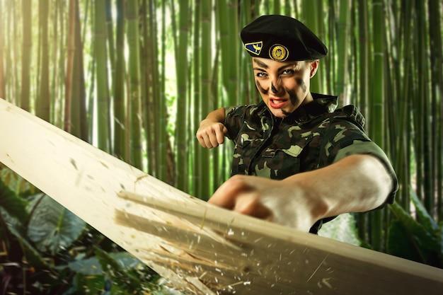 Mulher forte soldado do exército batendo em uma tábua de madeira