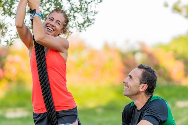 Mulher forte subindo em uma corda no parque e malhando com seu personal trainer.