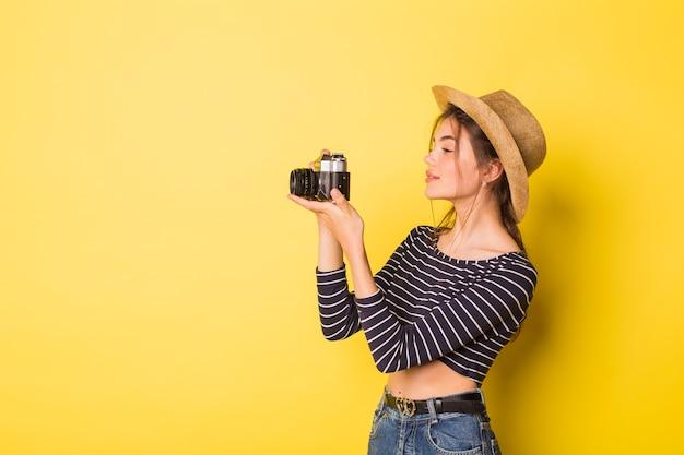 Mulher fotógrafa beleza caucasiana morena jovem em fundo amarelo