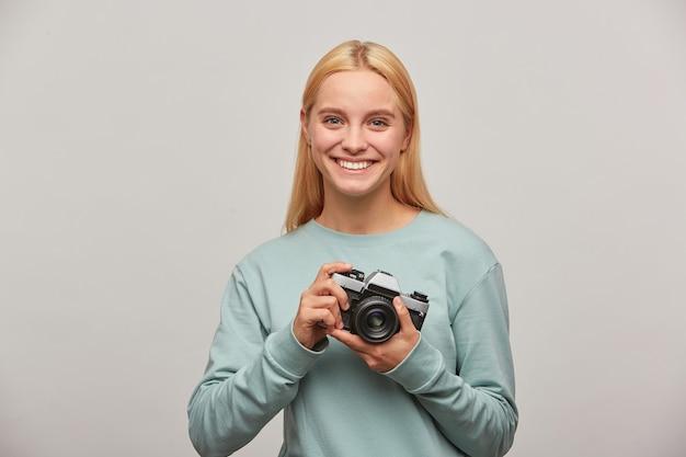 Mulher fotógrafa loira, com um sorriso simpático, parece feliz, encantada, segurando uma câmera fotográfica vintage retrô nas mãos