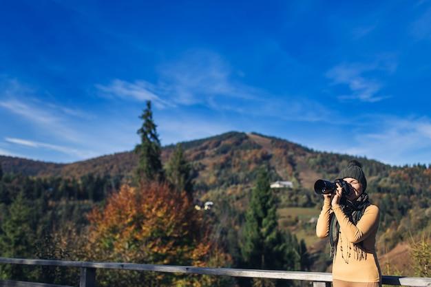 Mulher fotografa paisagem montanhosa de outono na câmera dslr.