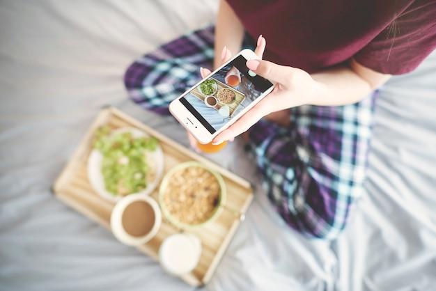 Mulher fotografando café da manhã na cama