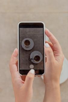 Mulher fotografando xícaras de café no smartphone