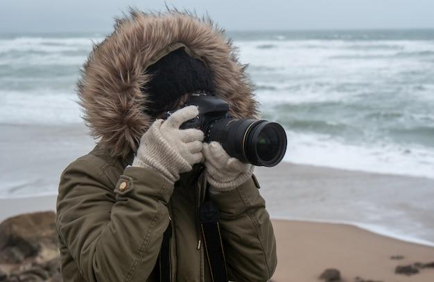 Mulher fotógrafo tirando uma foto na beira-mar no inverno