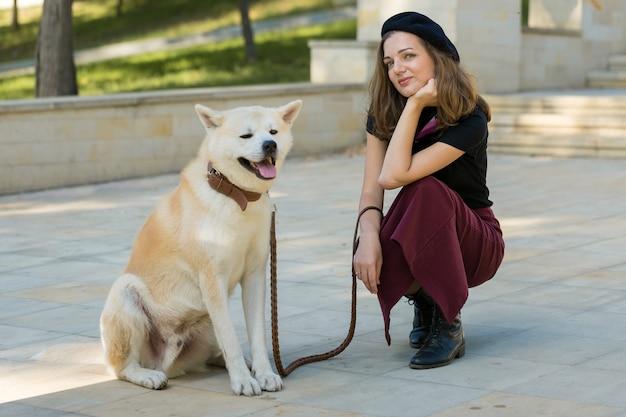 Mulher francesa elegante com um grande cachorro branco no parque