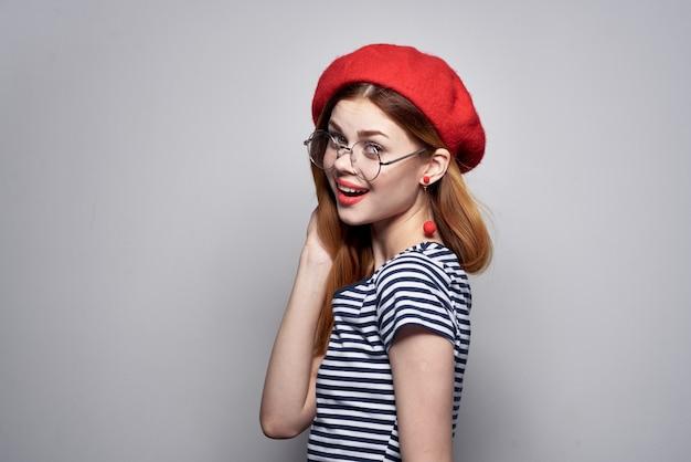 Mulher francesa em uma camiseta listrada gesto de lábios vermelhos com as mãos no verão