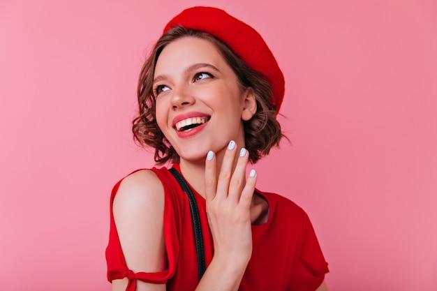 Mulher francesa feliz com manicure branca rindo. tiro interno da alegre garota encaracolada na boina vermelha, olhando para longe com um sorriso.