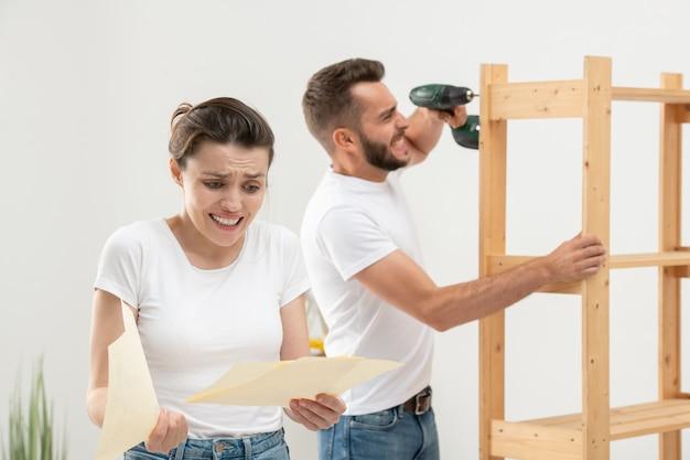 Mulher franzindo a testa intrigada, olhando para o plano de montagem com confusão, enquanto o marido irritado monta os móveis