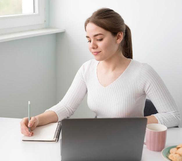 Mulher freelance de alto ângulo na mesa escrevendo na agenda