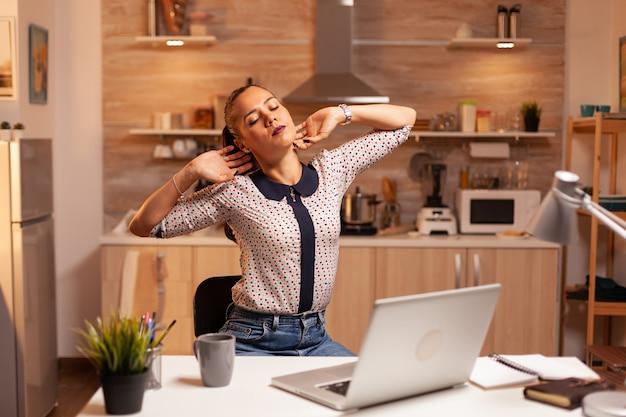 Mulher freelance esticando os braços por causa da exaustão enquanto trabalhava horas extras em casa. funcionário que usa tecnologia moderna à meia-noite fazendo horas extras para trabalho, negócios, ocupado, carreira, rede, estilo de vida