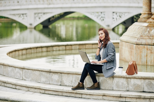 Mulher freelance sentada na fonte