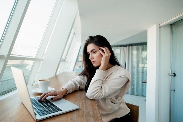 Mulher freelancer com dor de cabeça. mulher morena bebeu muito café e agora sofre de hipertensão. sala de luz branca no fundo. conceito de problemas de concentração.