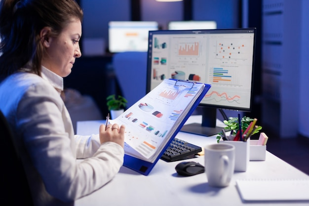 Mulher freelancer comparando gráficos da prancheta com gráficos do computador no escritório comercial
