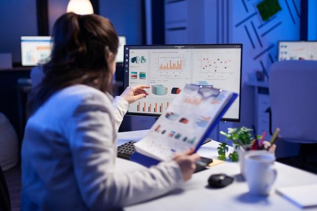 Mulher freelancer comparando gráficos da prancheta com gráficos do computador