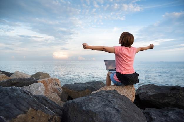 Mulher freelancer em camisa rosa comemorando levantou as mãos no céu.