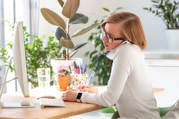 Mulher freelancer falando no smartphone, anotando com uma caneta, trabalhando no computador do escritório em casa