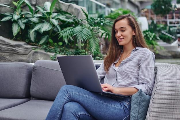 Mulher freelancer inteligente e moderna trabalhando remotamente on-line em um laptop