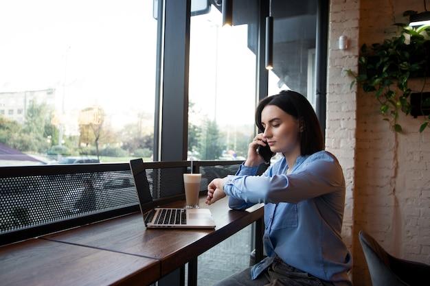Mulher freelancer ocupada olhando para o relógio e discutindo algo com o cliente